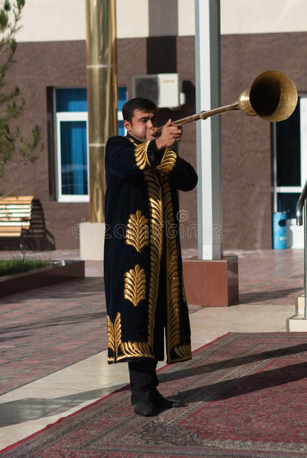 TASJKENT UZBEKISTAN - December 9 2011: Musikermän i traditionella kaftans som spelar det karnay royaltyfria foton