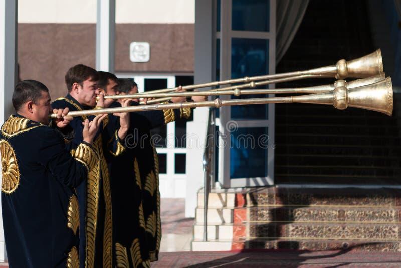 TASJKENT UZBEKISTAN - December 9 2011: Musikermän i traditionella kaftans som spelar det karnay arkivbild