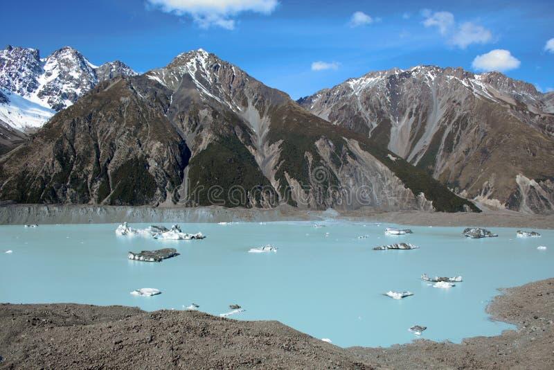 Tasman Glacier See während des sonnigen Tages mit Eisbergen auf Wasser und schneebedeckten Bergen im Hintergrund lizenzfreie stockbilder