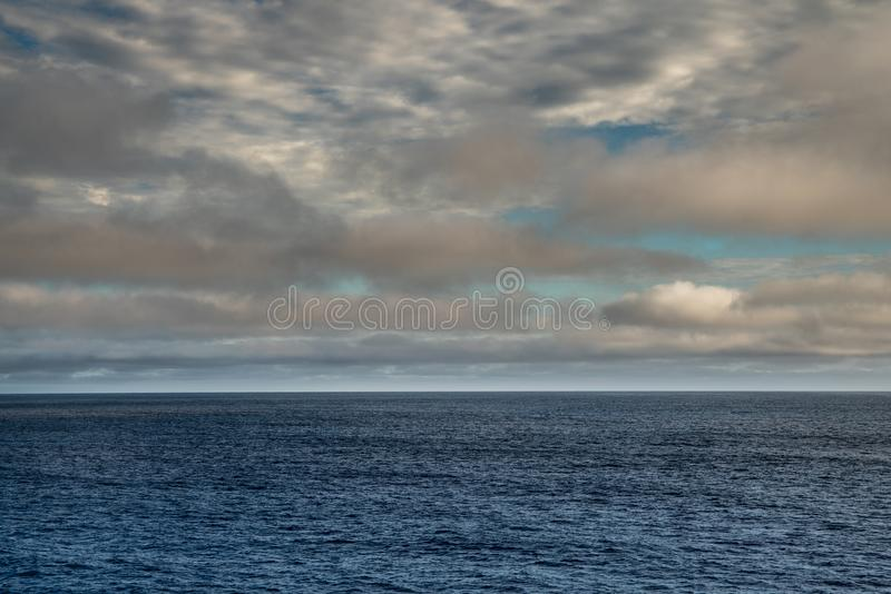 Cloudscape over Tasman Sea in morning, Tasmania Australia. Tasman Sea, Australia - March 20, 2017: Lower third of photo is blue sea water with low hanging brown royalty free stock photos