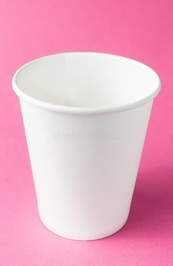 Tasse à emporter vide de café, de thé ou de jus sur le fond rose d'isolement, maquette vertical image libre de droits