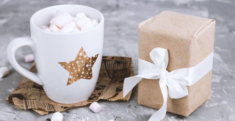 tasse élégante avec les guimauves et le fond gris concret de boîte-cadeau photographie stock