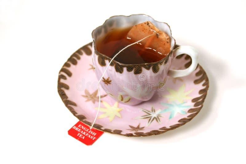 Tasse antique avec le sachet à thé. photographie stock