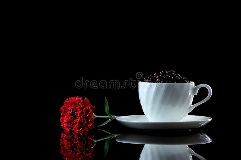 Tasse avec des grains de café et oeillet rouge sur un CCB réfléchi noir image stock