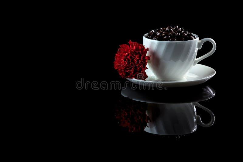 Tasse avec des grains de café et oeillet rouge sur un CCB réfléchi noir images stock