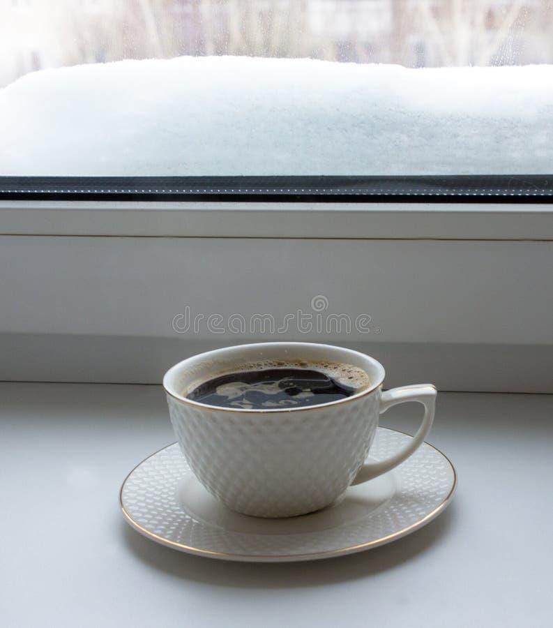 Tasse avec du café chaud sur des agains d'un rebord de fenêtre photo libre de droits