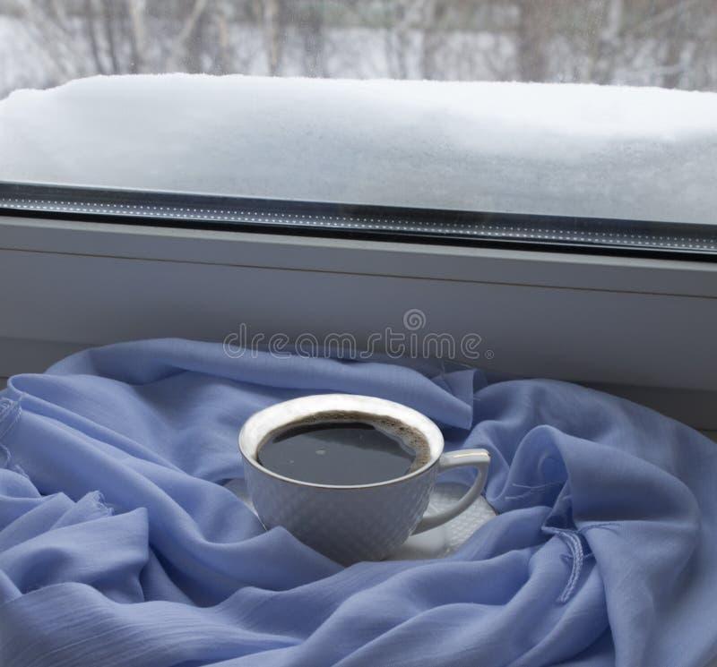 Tasse avec du café chaud sur un rebord de fenêtre contre image libre de droits