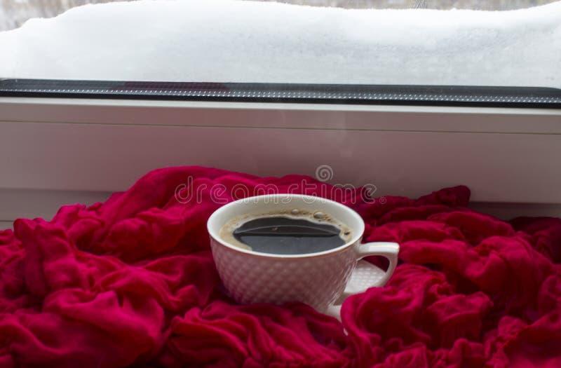 Tasse avec du café chaud sur un rebord de fenêtre contre photographie stock libre de droits