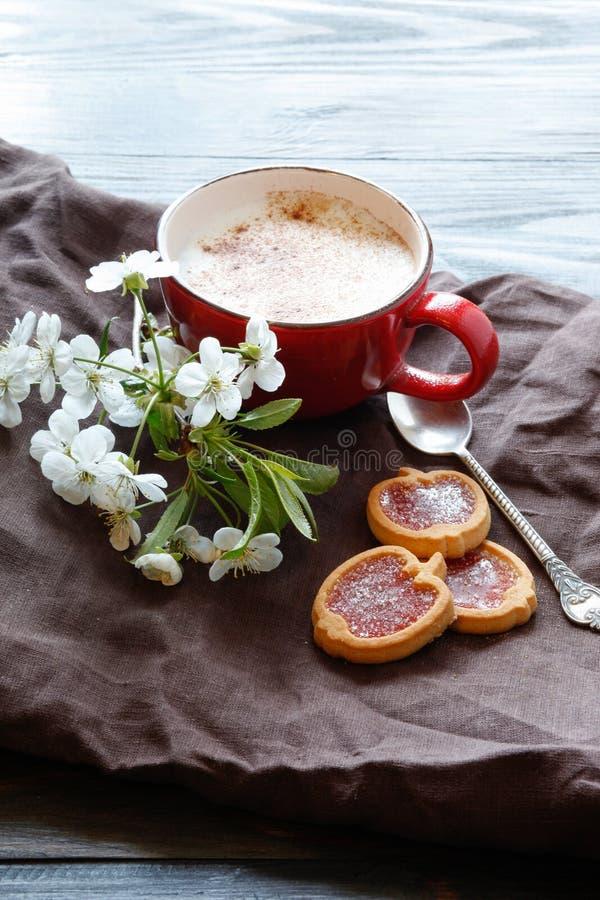 Tasse avec du café et fleurs de cerisier et biscuits photographie stock libre de droits