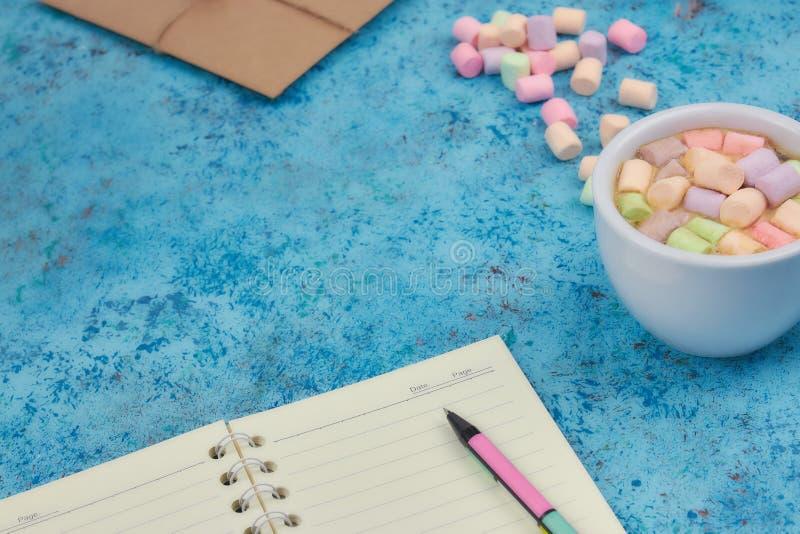 Tasse avec du café et les guimauves, carnet ouvert vide avec le stylo sur le fond bleu abstrait Vue supérieure Maquette plate L'e photographie stock