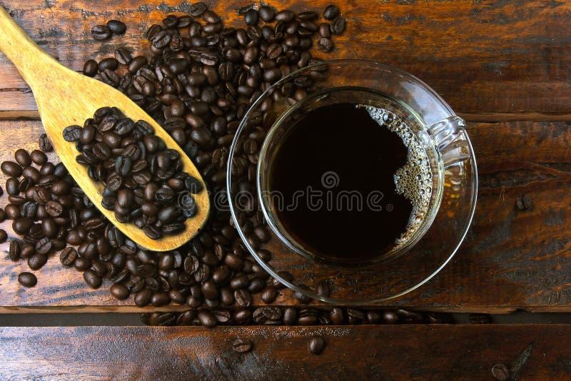 Tasse avec du café frais et des haricots rôtis renversés autour sur la table en bois rustique photographie stock