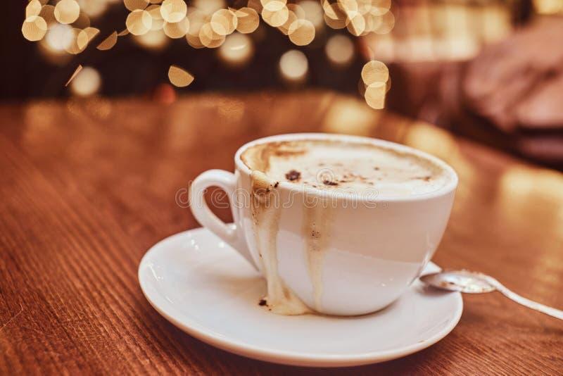 Tasse avec du café renversé sur la table en bois dans un café, fond de tache floue avec l'effet de bokeh photos libres de droits