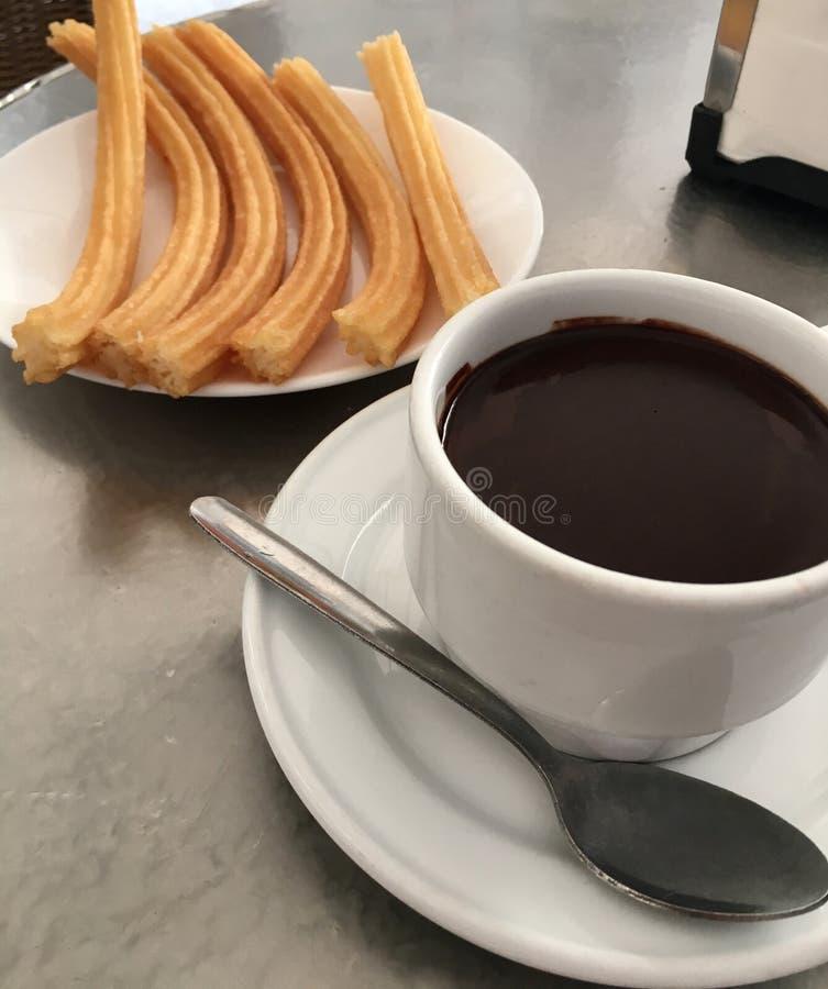 Tasse avec du chocolat chaud et le plat de churros photo stock