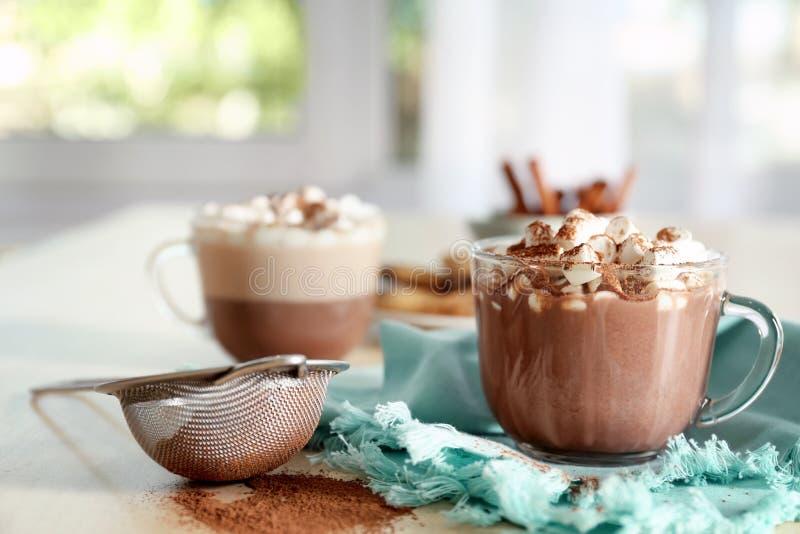 Tasse avec la boisson chaude avec les guimauves et la poudre de cacao sur la table image libre de droits