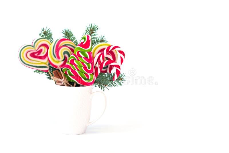 Tasse avec la branche d'arbre de sapin et les lucettes colorées sous forme d'arbre de Noël sur le fond blanc image libre de droits