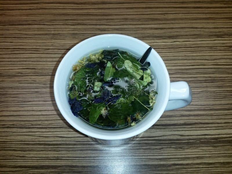 Tasse avec la cuillère et les herbes après le versement de l'eau pour le thé images stock