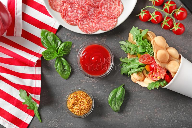 Tasse avec la gaufre et les sauces délicieuses de bulle sur la table grise photographie stock
