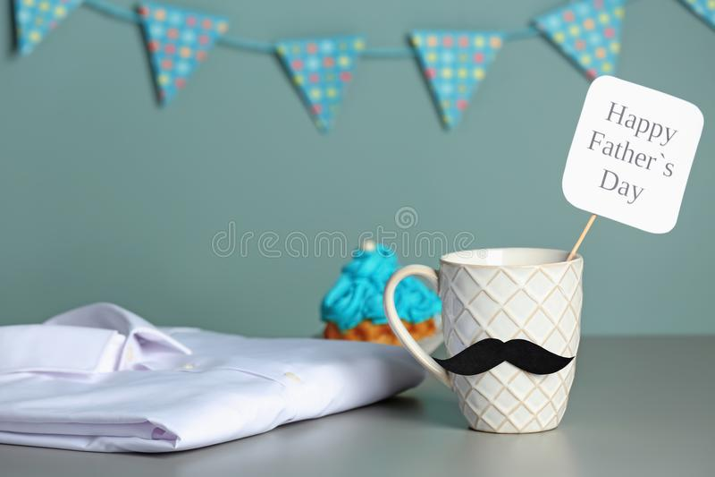 Tasse avec la moustache, le gâteau et la chemise sur la table photographie stock libre de droits