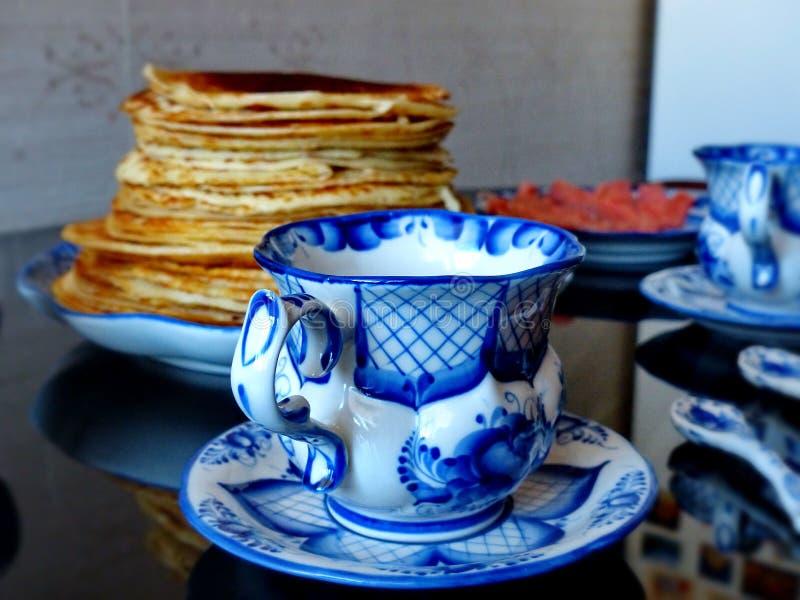Tasse avec la soucoupe et la cuillère à café le style de Gzhel sur le fond des crêpes russes de blinov Célébration de Maslenitsa  image stock