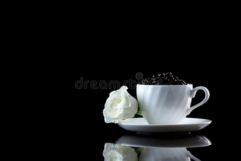 Tasse avec les grains de café et la rose de blanc sur un backgr réfléchi noir photos libres de droits