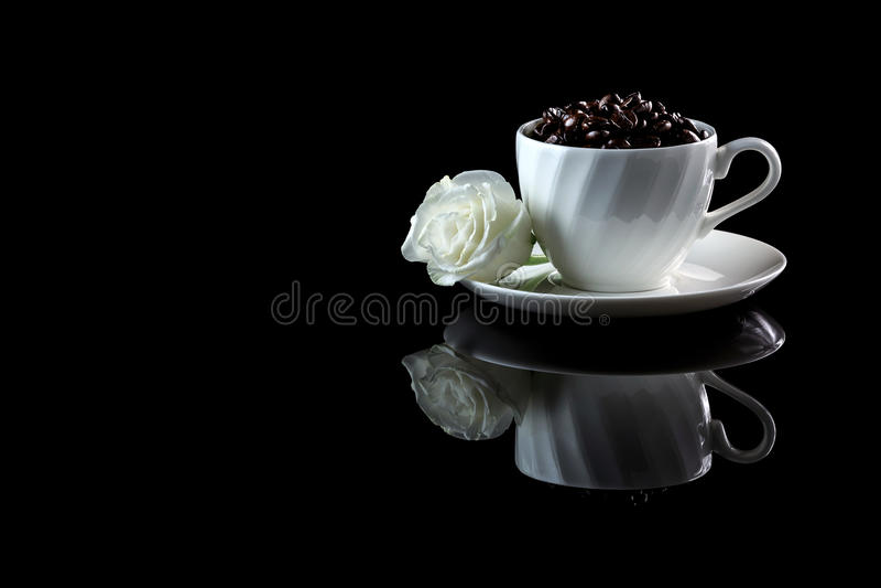 Tasse avec les grains de café et la rose de blanc sur un backgr réfléchi noir image stock