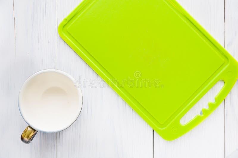 Tasse avec une planche à découper verte images libres de droits