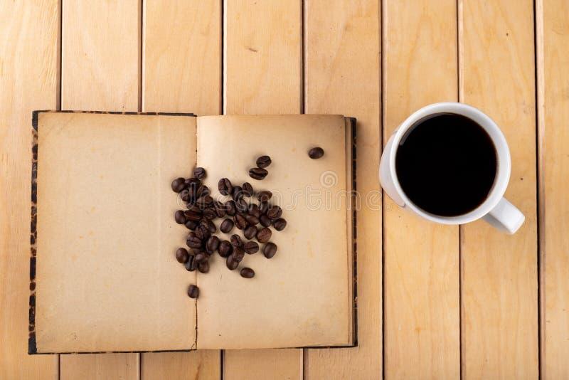 Tasse blanche avec du caf? noir sur une table en bois Grains de caf? sur un vieux livre image libre de droits