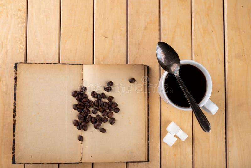 Tasse blanche avec du caf? noir sur une table en bois Grains de caf? sur un vieux livre images libres de droits