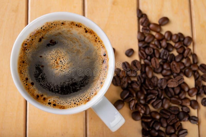 Tasse blanche avec du caf? noir sur une table en bois Un grain de caf? et d'une boisson chaude images stock