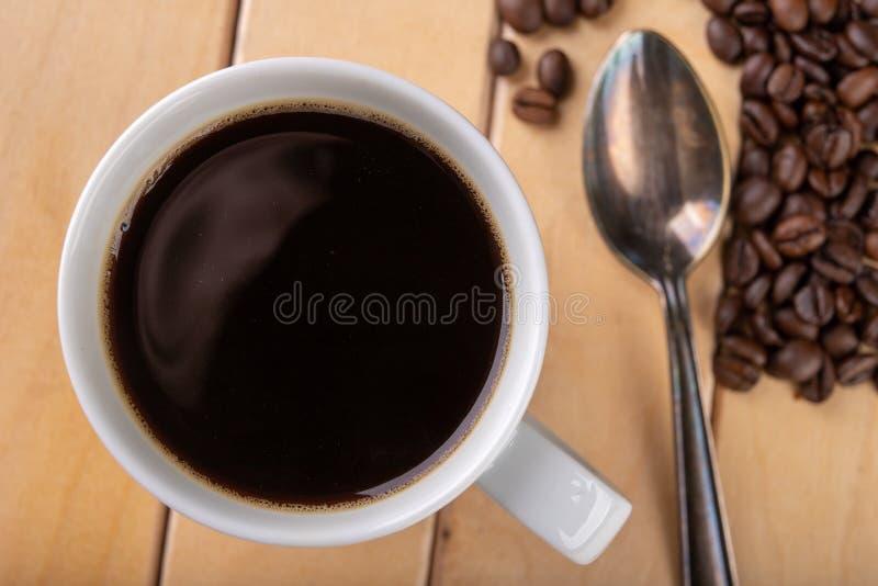 Tasse blanche avec du caf? noir sur une table en bois Un grain de caf? et d'une boisson chaude images libres de droits