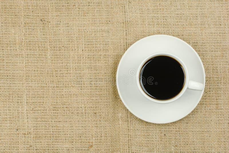 Tasse blanche avec la boisson de café sur le fond de toile à sac photos stock