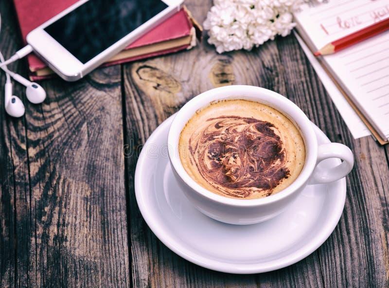 Tasse blanche avec le cappuccino derrière le téléphone portable images libres de droits