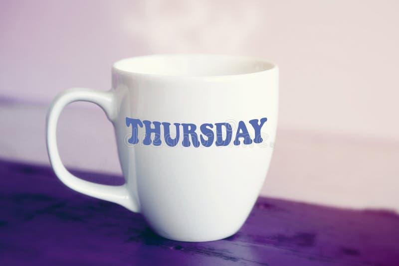 Tasse blanche avec le mot jeudi là-dessus photographie stock libre de droits