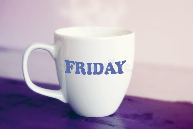 Tasse blanche avec le mot vendredi là-dessus photographie stock