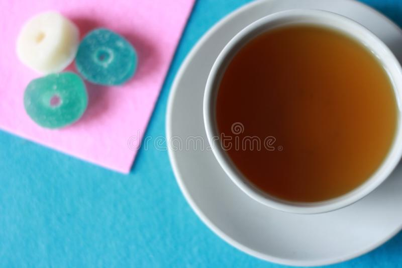 Tasse blanche avec le thé vert sur une soucoupe avec les bonbons multicolores à confiture d'oranges sur un rose et un fond senti  photos stock