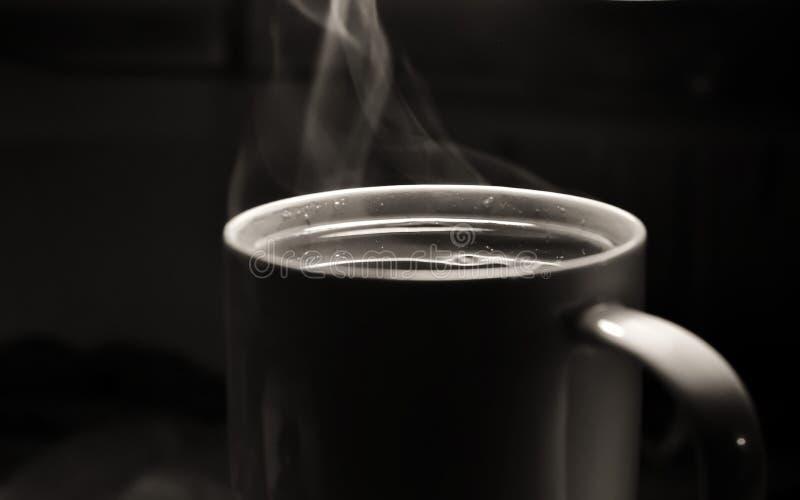 Tasse blanche avec un thé ou un café chaud de boissons avec de la fumée ou vapeur sur un fond foncé image libre de droits