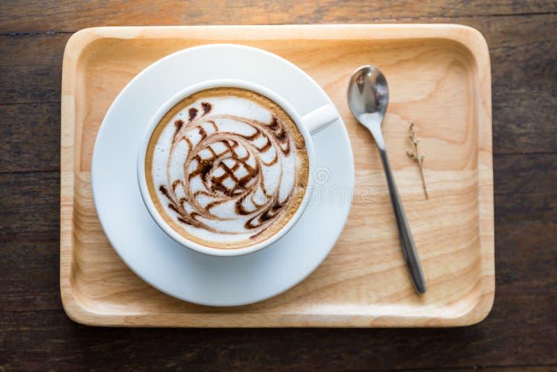Tasse blanche de café avec le beau modèle d'art dans la cuillère en bois de whute de plateau sur la table photos libres de droits