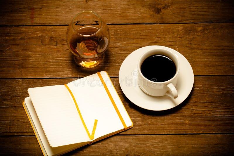 Tasse blanche de café, de cognac dans un verre et de carnet sur le vieux woode photo libre de droits