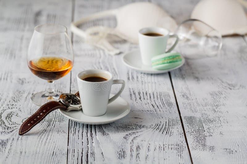 Tasse blanche de café et de cognac dans un verre sur la vieille table en bois image stock