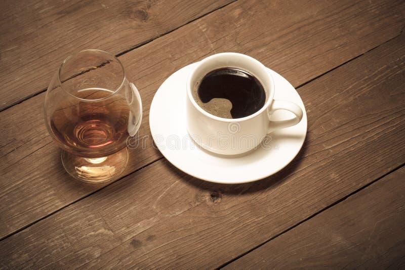 Tasse blanche de café et de cognac dans un verre sur la vieille table en bois T images stock