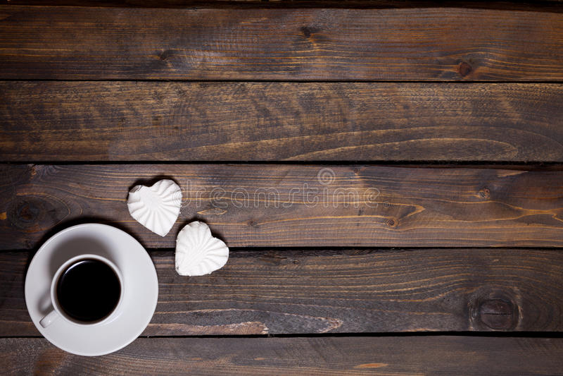 Tasse blanche de café et de deux guimauves sous forme de coeurs sur un fond en bois pour le petit déjeuner photographie stock