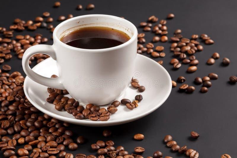 Tasse blanche de café fort en grains de café rôtis, sur un fond noir solide, premier plan, plan rapproché photos stock