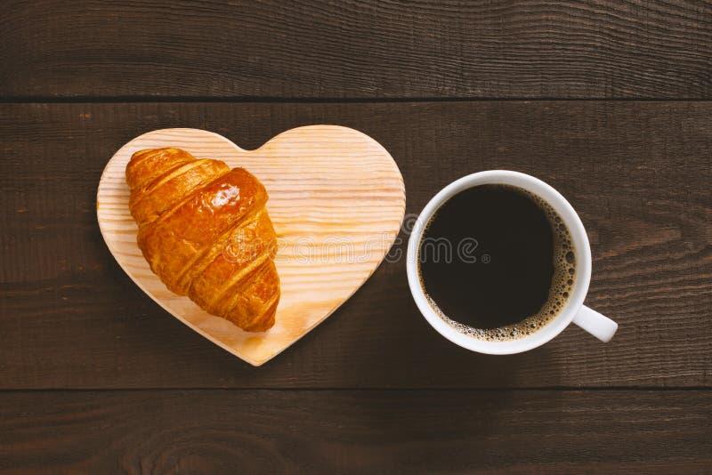 Tasse blanche de café noir avec le croissant frais photo libre de droits