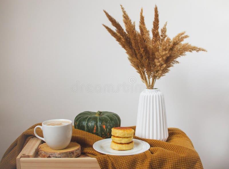 Tasse blanche de crêpes de fromage blanc de cappuccino de café, plaid jaune de couleur de moutarde, chambre à coucher images stock