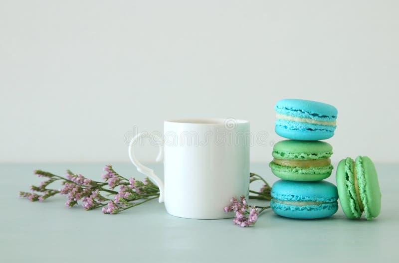 Tasse blanche de cru de café et de macaron coloré ou macaron au-dessus de table en bois en pastel images libres de droits