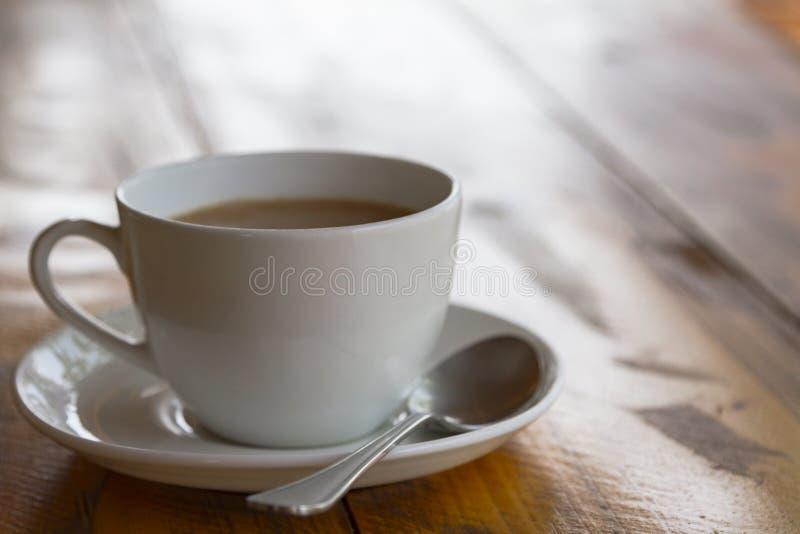 Tasse blanche de masala indien traditionnel de thé avec le sauser et le spon photographie stock libre de droits