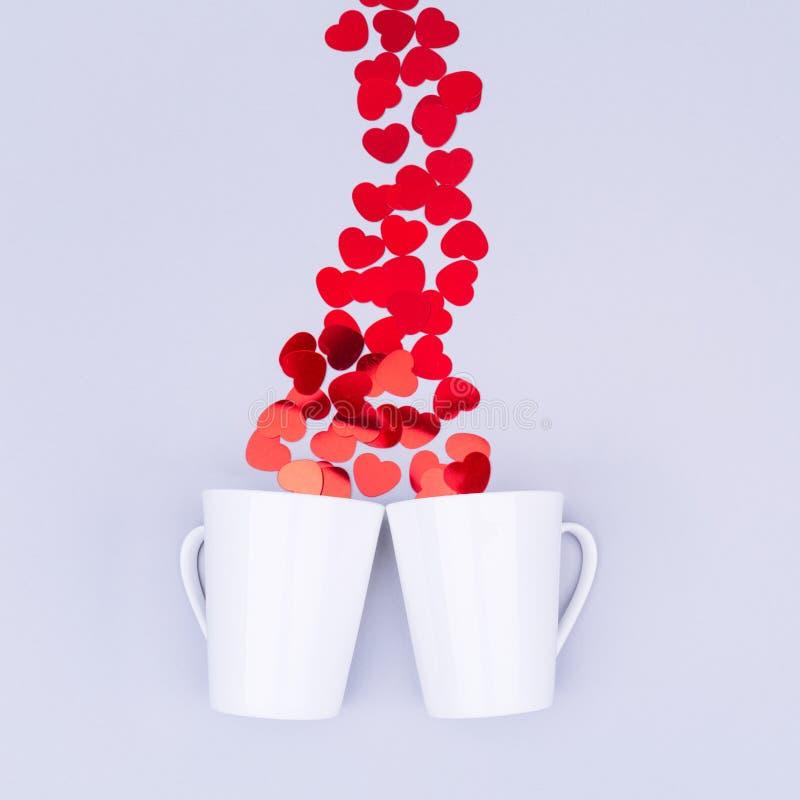 Tasse blanche de porcelaine avec des confettis de coeur de scintillement Saint Valentin concentré images libres de droits