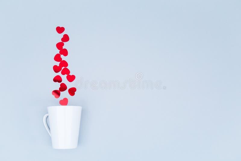 Tasse blanche de porcelaine avec des confettis de coeur de scintillement Saint Valentin concentré images stock