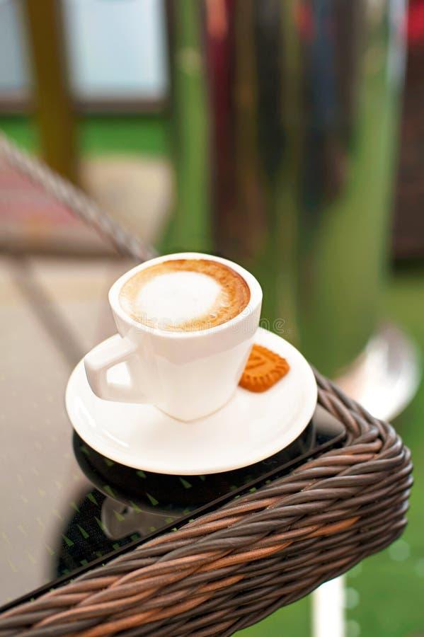 Tasse blanche de porcelaine de café noir avec du lait sur la table de rotin photos stock