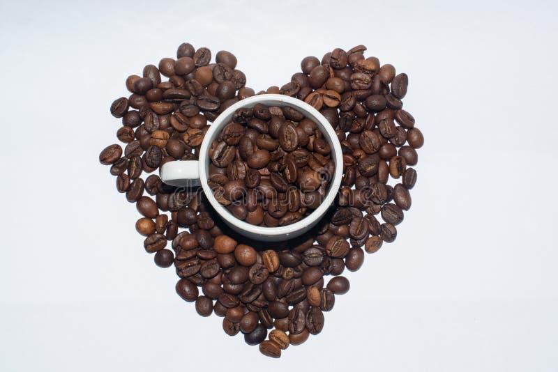 Tasse blanche de porcelaine complètement de grains de café images libres de droits